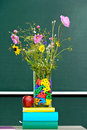 Flowers in a classroom vase decorated with alphabetical letters with an apple on teachers desk front of board Stock Image