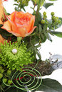 Flowers in a creative wedding display with spiral wires and pearl on greenery with an orange rose Royalty Free Stock Image