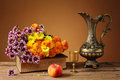 Flowers and a metal jug on the table Stock Photo