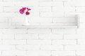 Flowers on a shelf decorative white brick wall with in vase it Stock Photos