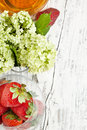 Flowers and strawberries on white wood Royalty Free Stock Image