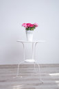 Flowers on the table pot with colorful red and pink rose standing a white in minimalistic style in an empty room against wall Royalty Free Stock Photo