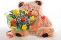 Flowers and a teddy bear with bouquet of Stock Images