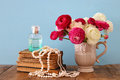 flowers in the vase next to old books, pearls necklace and perfume bottle Royalty Free Stock Photo