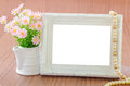 Flowers vase and vintage white picture frame. Royalty Free Stock Photo
