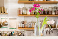 Flowers in vases in a white kitchen with wooden shelves stocked with spices Royalty Free Stock Photo