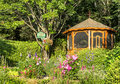 Flowery gazebo with bird house flower trees Stock Photos