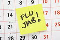 Flu jab reminder the phrase written on a yellow post it note and stuck to a wall calendar to remind the elderly and people with Royalty Free Stock Photos