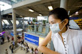 With flu mask at the airport Royalty Free Stock Image