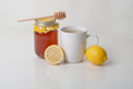 Flu medicine herbal tea with honey lemon a display of a cup of a fresh and a jar of a drizzler on top on a white background Stock Photo