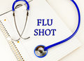 Flu shot text over a white notebook wrapped in a blue stethoscope Royalty Free Stock Photo