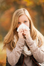 Flu young girl with handkerchief in autumn scenery Stock Photography