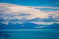 Fluffy clouds hover over the bay and the mountains. Shevelev.