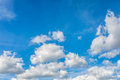 Fluffy white clouds in a sunny blue sky Royalty Free Stock Photo