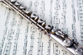 A flute on sheet music Royalty Free Stock Images