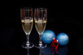 Flute with sparkling and christmas balls on black Royalty Free Stock Photo