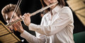 Flutist on stage elegant female performing with orchestra Stock Photo