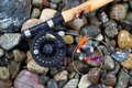 Fly Fishing Pole and Reel with Flies on Wet Stones Royalty Free Stock Photo