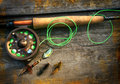 Fly fishing rod with polaroids pictures on wood Stock Photo