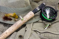Fly fishing still life rod and reel with lures against vest and hat Royalty Free Stock Image