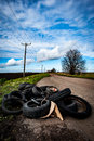 Fly tipping tipped worn out tyres left on a country lane Royalty Free Stock Photos