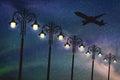 Flying aircraft and vintage lampposts at night Royalty Free Stock Photo
