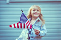 Flying american flag in little girl's hand selective focus blurred background independence day day concept vintage and Stock Photography