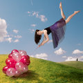 Flying girl holding colourful balloons Royalty Free Stock Photo
