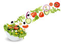 Flying green salad in bowl with tomatoes, onion, olives and cucu Royalty Free Stock Photo