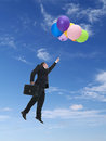 Flying high businessman wearing black suit holding suitcase in the air being raised by bunch of colorful balloons Stock Image