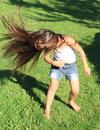 Flying long hair brown of a little barefoot girl in air Stock Images