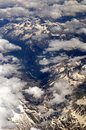 Flying over the alps to rome air travel europe toward italy with snow covered mountains and light cloud Stock Photo