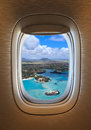 Flying over tropical beach view of porthole of the plane over idyllic island Stock Photo