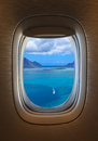 Flying over tropical beach view of porthole of the plane over idyllic island Royalty Free Stock Image
