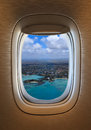 Flying over tropical beach view of porthole of the plane over idyllic island Royalty Free Stock Images