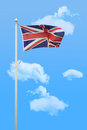 Flying union jack in the wind against blue summer sky Royalty Free Stock Images