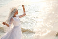 Flying veil happy bride is standing near sparkling water and holding her Stock Photo