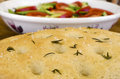 Focaccia bread freshly baked on a wooden board served with greed salad Royalty Free Stock Photos