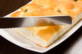 Focaccia with green olives focaccia is flat oven baked italian bread on the wood table knife Stock Photos