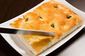 Focaccia with green olives focaccia is flat oven baked italian bread on the wood table knife Stock Photo