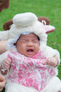 Focus at Asian newborn baby girl with costumes little sheep in the garden and mother is holding her.