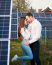 Loving couple embracing enjoying each other on background of row solar panels at plantation near the house