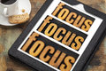 Focus concept on digital tablet word in and out of text in vintage letterpress wood type a with a cup of coffee Royalty Free Stock Photography