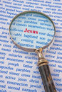Focus on jesus text in red surrounded by words in blue relating to his life story a hand magnifier focuses attention the name Royalty Free Stock Photography