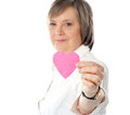 Focus on pink paper heart. Aged woman holding it Royalty Free Stock Photo