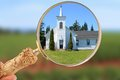 Focus on religion magnifying glass focusing in showing a quaint rural church Stock Photos