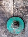 Focus of vintage green bolt on vintage wood