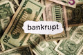 Focus on the word bankrupt on piece of torn white paper with blu blur banknotes currency as a background concepts finance and Royalty Free Stock Photography