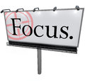 Focus word billboard aiming goal concentrate mission a large white with the and a target reticle to illusstrate the importance of Royalty Free Stock Image