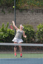 Focused on the ball toss tennis player trying to strike at height of Royalty Free Stock Photography